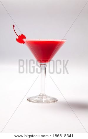 Red Drink In Martini Glass, Garnished With Marachino Cherry. On White Background