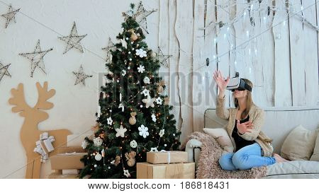 Woman using virtual reality glasses. Virtual reality mask. VR. Christmas, future and technology concept