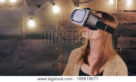 Young woman using Virtual Reality Glasses. Virtual reality mask. VR. Retro loft Christmas background with light bulbs