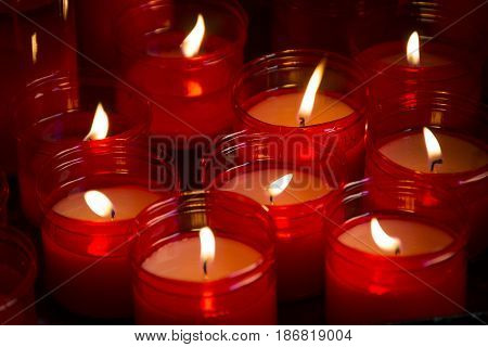 Large group of red candles shining in the dark