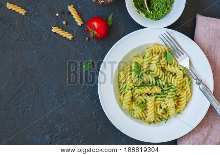 Top View Of Pasta Pesto Sauce Served In A White Plate On A Black Slate Background. Copy Space.
