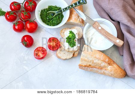 Set Of Ingredients For Bruschettas With Goat Cheese, Pesto Sauce And Tomatoes Abd Baguettes On A Whi