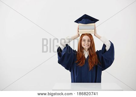 Ginger girl graduate smiling holding books on head under cap sitting over white background. Copy space.