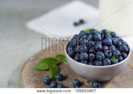 Freshly picked juicy blueberries with green leaves on rustic table.