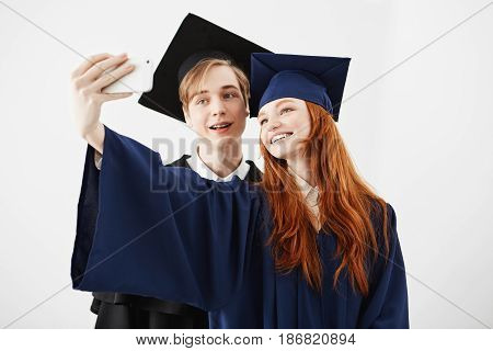 Beautiful friends graduates of college in caps smiling making selfie over white background.