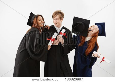 Cheerful graduate classmates with diplomas celebrating smiling rejoicing over white background.