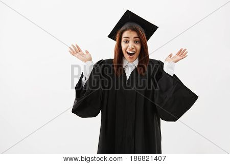 Happy surprised girl graduate gesturing looking at camera over white background. Copy space.