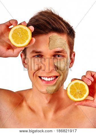 Facial mask from fresh fruits and clay for man concept. Face with treatment mud applied. Male holding lemon half for skin care procedure in salon. Young guy is smiling happily.