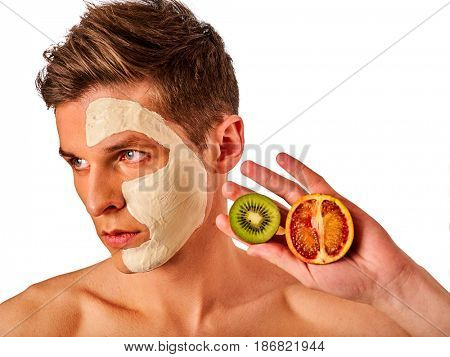 Facial mask from fresh fruits and clay for man concept. Face with treatment mud applied . Male holding lemon half for skin care procedure in salon. Fresh fruits as a symbol of the spa salon.