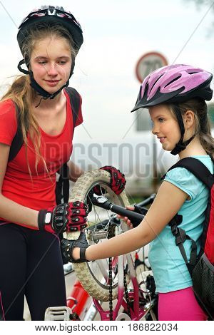 Bicycle tire pumping by child bicyclist. Girl wearing bicycle helmet with hand pump . Kids pump up tire. There are road and traffic sign at background. Children return home from school on bicycles.