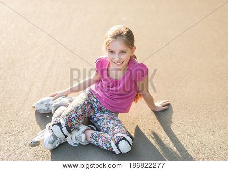 Lovely girl rollerblading sitting on asphalt in the alley of the park, stretching