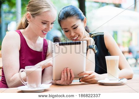 Two young female best friends smiling while using a tablet PC outdoors at a trendy location downtown