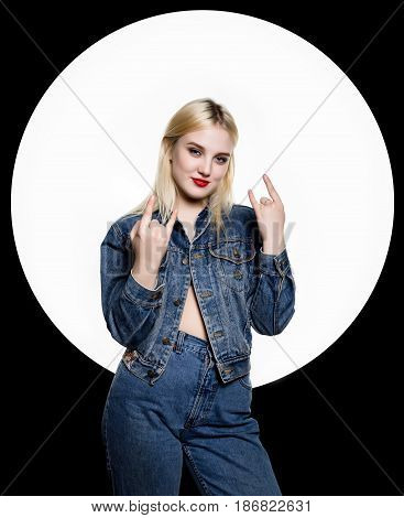 young hooligan in jeans and a denim jacket shows different signs with her fingers.