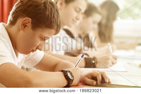 Students or pupils writing test in school being concentrated