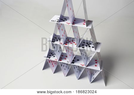 casino, gambling, games of chance, hazard and insecurity concept - close up of house of playing cards over white background