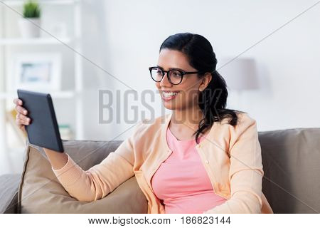 people, technology and leisure concept - happy young indian woman sitting on sofa with tablet pc computer at home