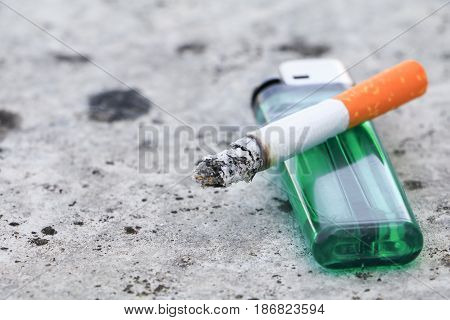 cigarette burn and lighter on floor concrete background. concept Non-smoking day universal