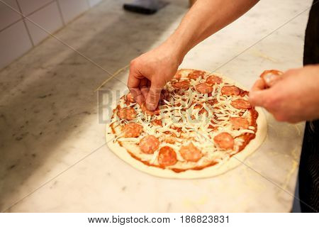 food, culinary, italian cuisine, people and cooking concept - cook hands adding salami slices to pizza at pizzeria