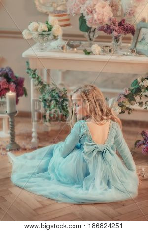 the flower Studio is sitting on the floor blonde girl in blue long dress and with a flower on the head