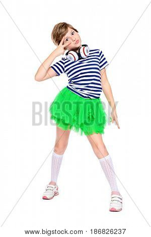Cool nine year old girl enjoys the music in headphones. Copy space. Full length studio portrait. Isolated over white.