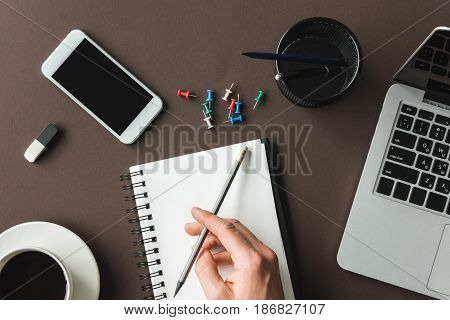 Close-up Partial View Of Person Holding Pencil And Writing In Notebook At Desk With Laptop, Smartpho