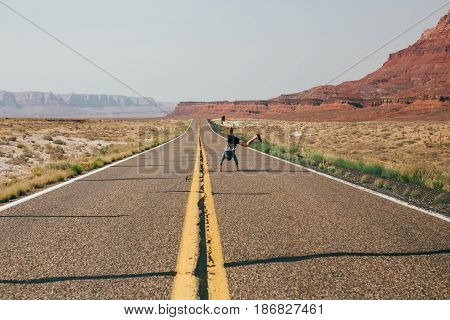 Young traveller rests in middle of his journey through the roads and valleys of united states by making a silly joke and wheel