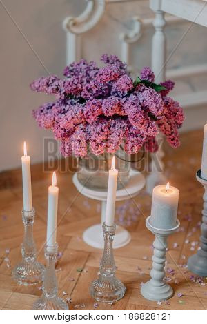 on the parquet floor candle stand with candles and a bouquet of lilacs