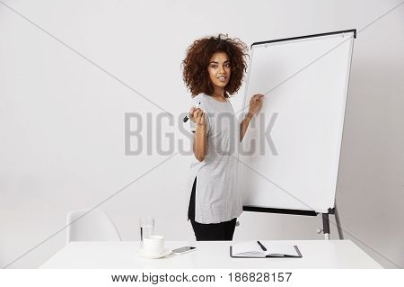 African businesswoman smiling standing near marker whiteboard in office. Copy space.