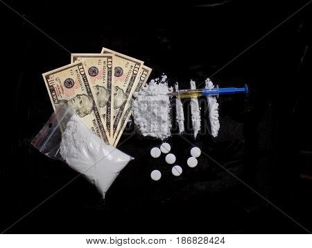 Injection syringe on cocaine drug powder pile and lines, pills, cocaine bag, dollar money bills on black background