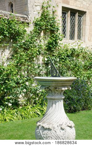 Sundial on lawn  with old house in background