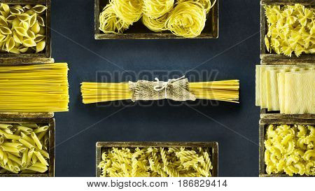 Different kind of Italian pasta in wooden boxes on a dark blue background
