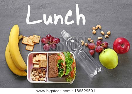 Concept of school lunch. Lunchbox and food on gray background