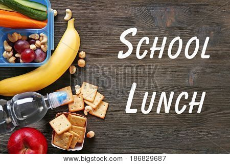 Concept of school lunch. Lunchbox and food on wooden background