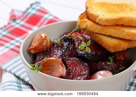bowl of baked beetroot with garlic and toasts on checkered dishtowel - close up