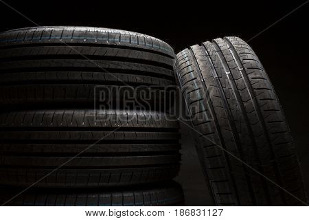 Stack of brand new high performance car tires on clean high-key white studio background
