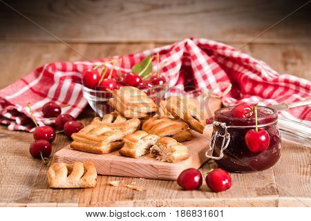 Cherry pastry pies with fresh cherries on cutting board.