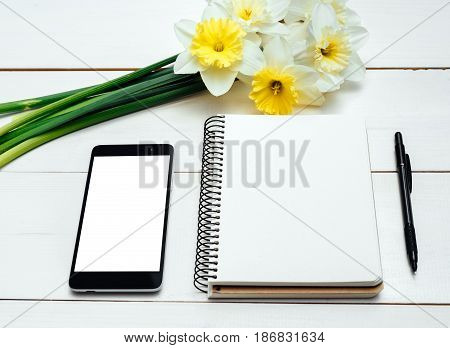 Yellow bouquet of narcissus on white wooden background. Blank card flat lay. Top view on table with narcissus empty diary pencil and phone free space