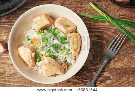Plate with tasty chicken and rice on wooden table