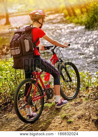 Bicycle teen with ladies bikes in summer park. Womens road bike for running on nature. Teenager girl in helmet cycling fording throught water. Girl thinks how to cross river outdoor.