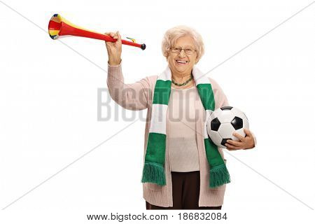Mature female soccer fan with a trumpet and a football isolated on white background