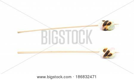 Single slightly burnt on fire marshmallow candy on a wooden grill stick isolated over the white background, set of two different foreshortenings