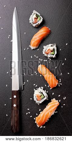 Sushi nigiri sushimi with salmon and roll sushi philadelhia with knife for sushi. Over stone background.Copy space .Sushi menu. Japanese food.Top view.