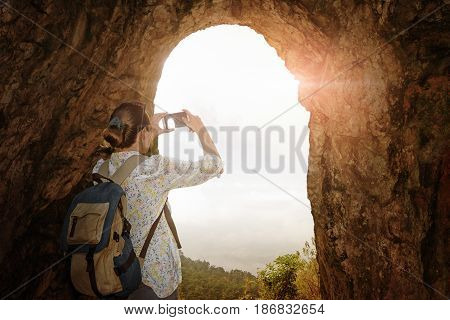 tourist with backpack photographing on the smartphone mountain landscape from the cave. Summer holiday travel and technology outdoors.