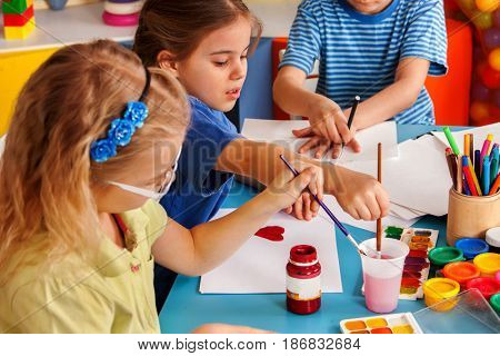 Small students girls painting in art school class. Children boy and girl drawing by paints on table. Children have fun at the children's club. Craft drawing education develops creative abilities of