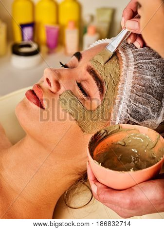 Mud facial mask of woman in spa salon. Massage with clay full face. Girl on with therapy room. Female lying wooden spa bed. Beautician with brush therapeutic procedure isolated background. Home mask.