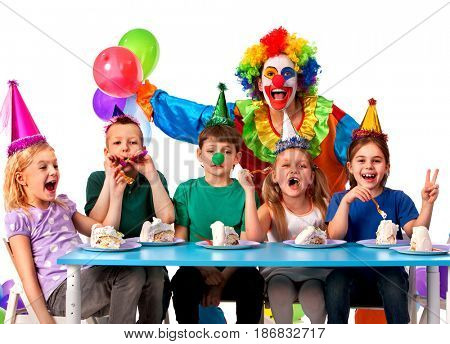 Birthday child clown playing with children who eat cake. Kid with nose bunny fingers prank. Fun of group people pose for camera sit at table white background. Eating a holiday cake.