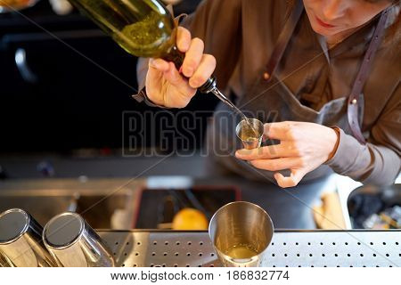 drinks, people and luxury concept - woman bartender with shaker pouring alcohol into jigger and preparing cocktail at bar counter