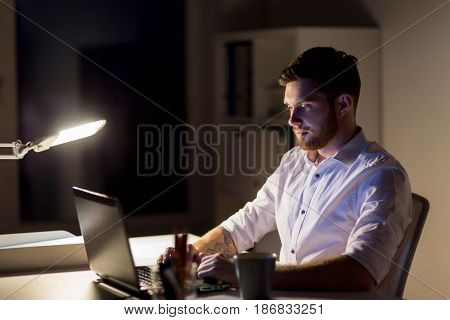 business, overwork, deadline and people concept - man with laptop and coffee working late at night in office