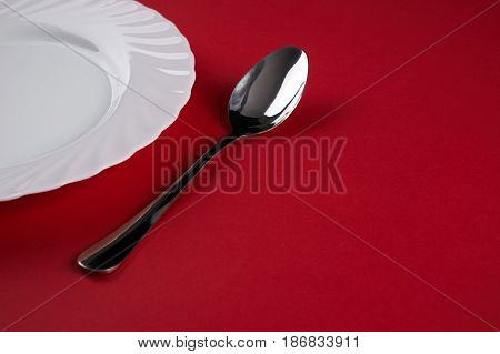 Empty white dinner plate with silver fork and Dessert Tablespoon isolated on red tablecloth background with copy space. Table Setting. Dinner place setting