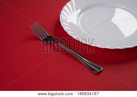 Empty white dinner plate with silver fork isolated on red tablecloth background with copy space. Table Setting. Dinner place setting